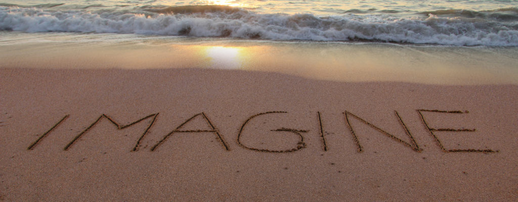 Imagine written in the sand on a sunset beach.